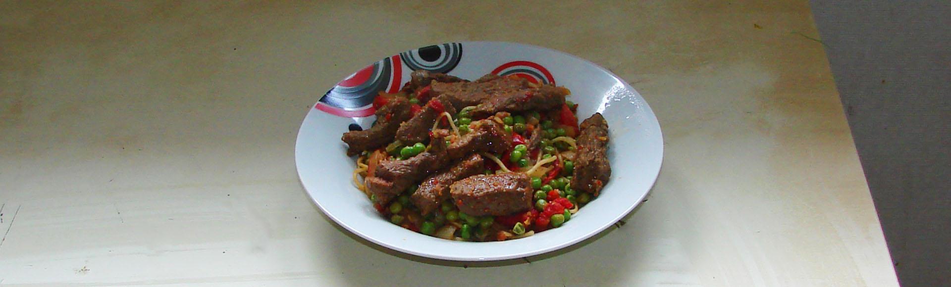 Nouilles chinoises sautées au boeuf, poivrons grillés et petits pois